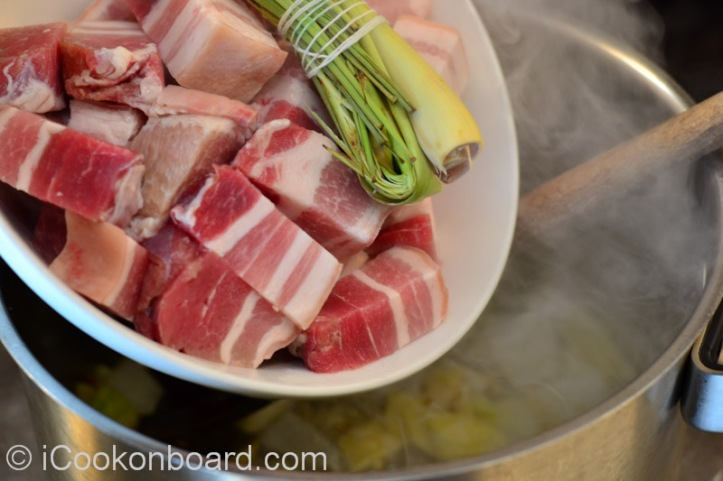 Add the pork belly and lemongrass.