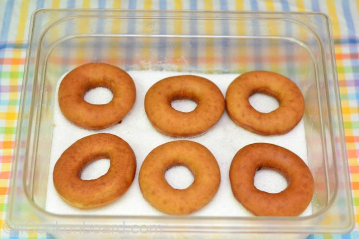 Place the sugar for coating in a bowl or container with lid.  Put the donuts inside the sugar bowl/container.