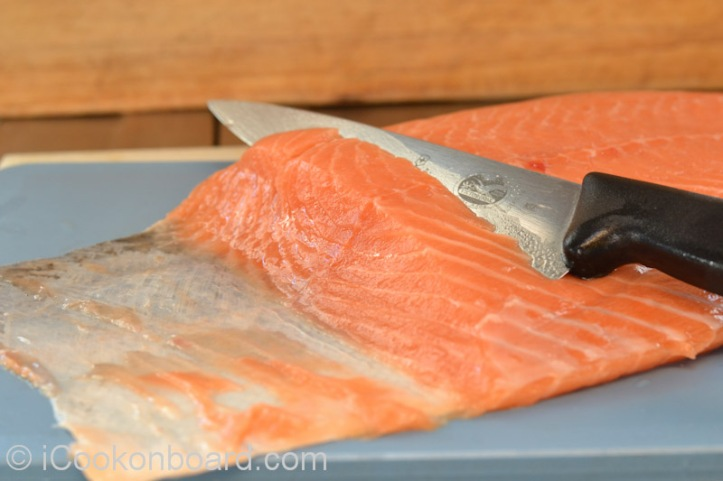 Use a fillet knife if available. Lie salmon fillet  on chopping board skin side down.