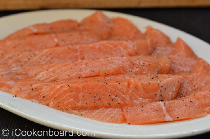 Season sliced salmon fillet with fine salt and freshly grounded black pepper.