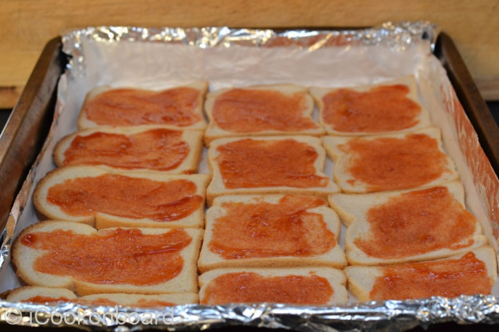 Place Tasty bread on a large tray.  Brush with pizza sauce.