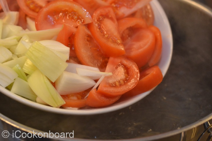 Place the water on a high soup pot and bring to a boil on very high heat. Add the onion and tomatoes.