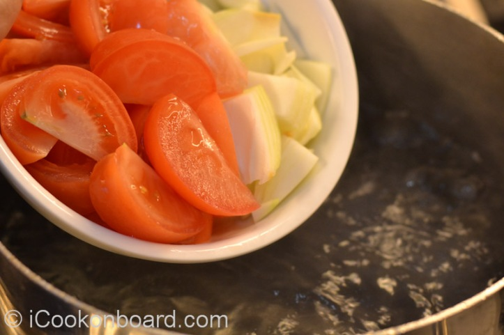 On a large soup pot, bring water to a boil and add the onions, tomatoes and taro.