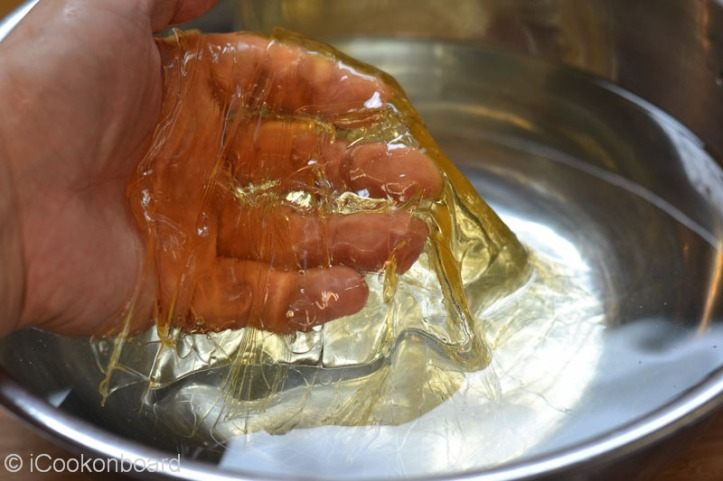 Take out gelatine sheets from water, squeeze with your hands...