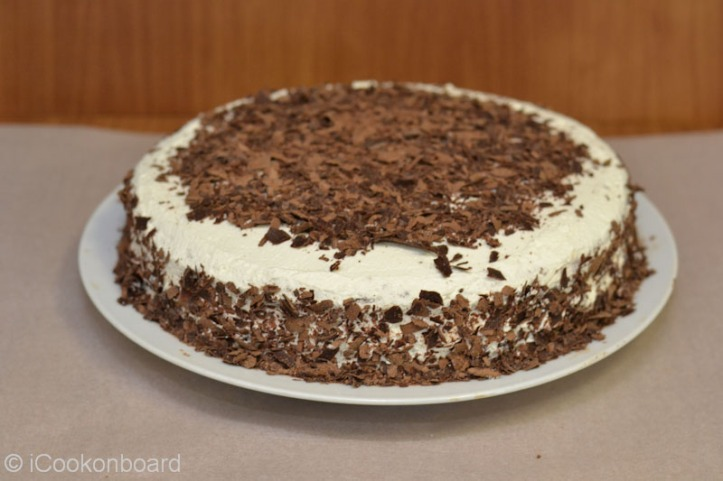 Gently sprinkle the remaining choco shavings around the sides of the cake.